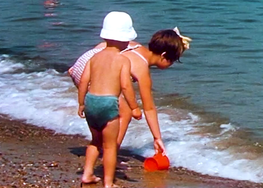children playing at the water's edge at the seaside